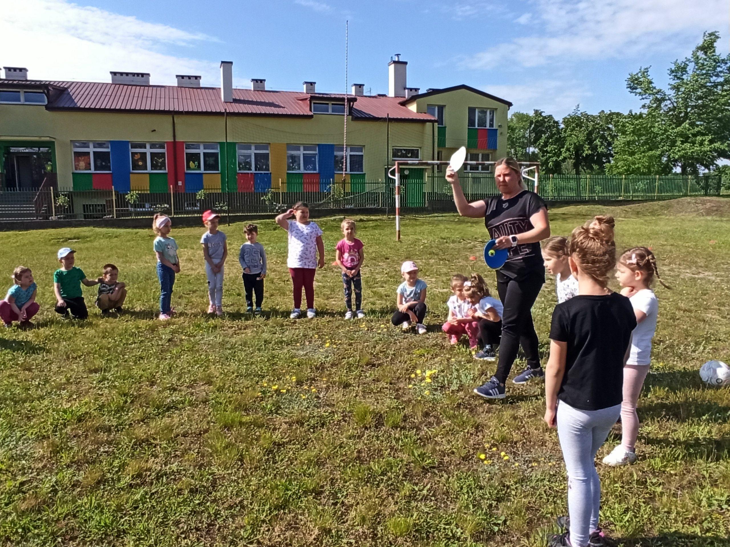 zdjęcie przedstawia dzieci podczas zajęć z nauczycielem wychowania fizycznego -p. Moniką